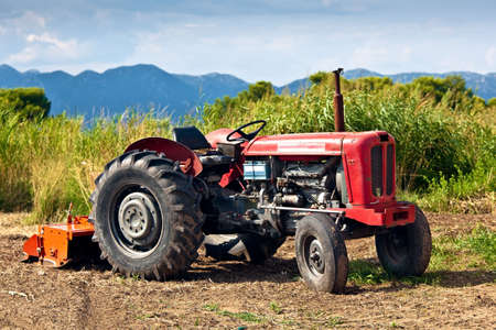 Old tractor but still operating on the field Stock Photo