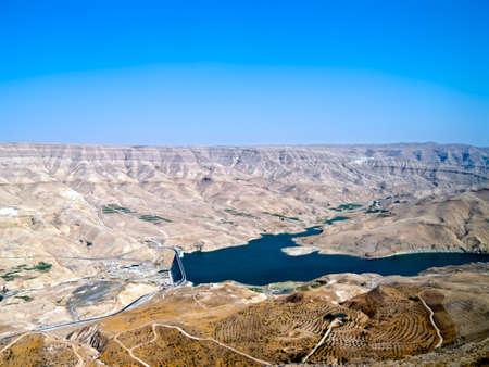 street wise: Wadi Mujib - King s road area, highway on the water dam with desert landscape around it in Jordan. Stock Photo