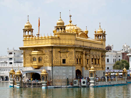 temple tower: Golden Temple. Holiest shrine of the Sikh religion. Ornate gold covered building in the middle of an artificial lake in Amritsar, Punjab, India.