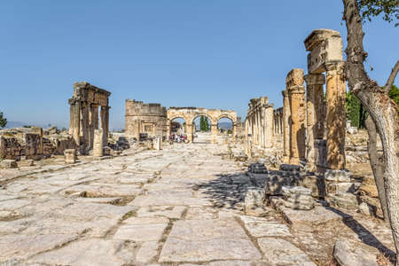 thoroughfare: Frontinus street, the main thoroughfare and Fortinus gate at the end. Roman time city Hierapolis, Pamukkale, Turkey.