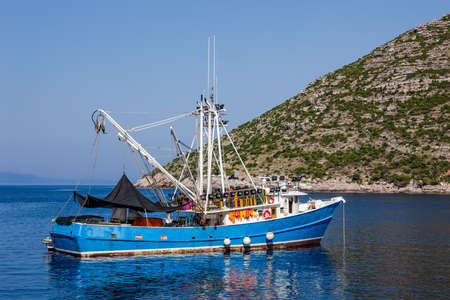 Typical Mediterranean fishing boat in the sea near coast preparing for fishing. Location Peljesac peninsula, Croatia photo