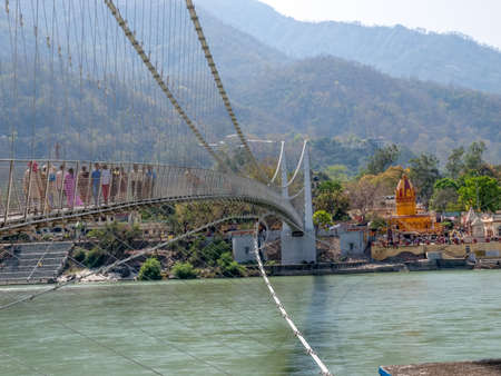 Bridge Laxman Jhula with Pedestrians, on the Holy Ganges river  that flows through Rishikesh (the world capital of Yoga) - the holy city for the Hindus, India. photo