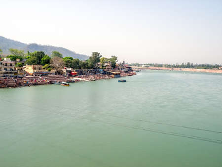 ancient yoga: Panorama view of the Holy Ganges river that flows through Rishikesh - the holy city for the Hindus, India. Shoot from Bridge Laxman Jhula.