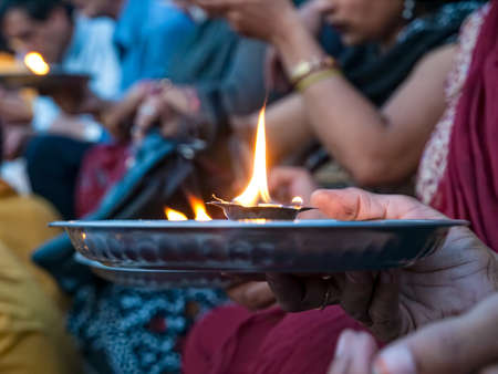 Hindu prayer ritual - detail with hand holding ceremonial fire, Rishikesh India.