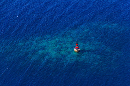 Aerial helicopter shoot of small red lighthouse in front Cavtat town. Adriatic sea, Croatia photo