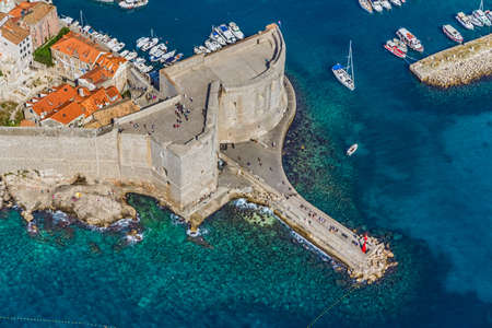 Aerial helicopter shoot of Dubrovnik old town. Walls detail -St. John Fortress with entrance to the old city port.
