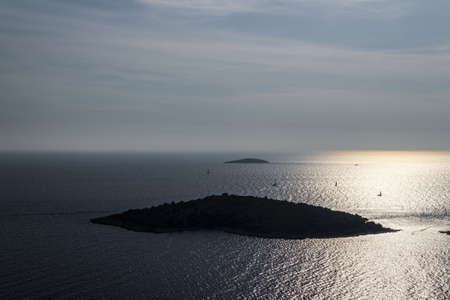 Aerial helicopter picture of an island with a sun backlight Stock Photo - 16694360