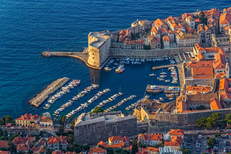 Early morning sunrise - panorama with Dubrovnik old city defense walls details.  St. John fortress at the harbor entrance. Location Croatia - Europe.