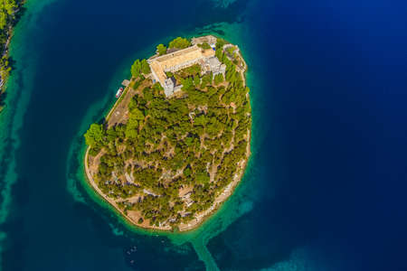 Aerial helicopter shoot of National park on island Mljet, Dubrovnik archipelago, Croatia. The oldest pine forest in Europe preserved and Monastery of Saint Mary on a small island in a big lake. photo
