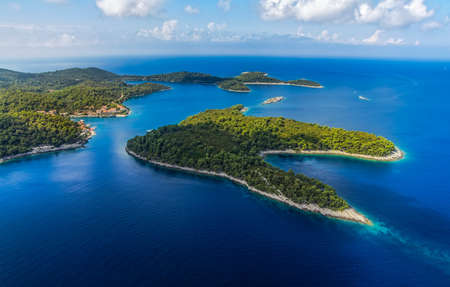 croatia dubrovnik: Aerial helicopter shoot of National park on island Mljet, village Pomena, Dubrovnik archipelago, Croatia. The oldest pine forest in Europe preserved. Stock Photo