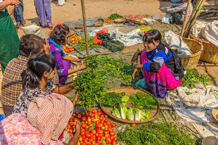 BAGAN, MYANMAR - FEBRUARY 24: Women are selling vegetables at the local market on February 24, 2012 in Bagan, Myanmar. All the food is organically grown.