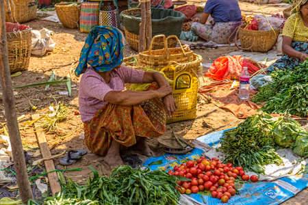 BAGAN, MYANMAR - FEBRUARY 24: Women are selling vegetables at the local market on February 24, 2012 in Bagan, Myanmar.