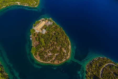 Aerial helicopter shoot of National park on island Mljet, Dubrovnik archipelago, Croatia  The oldest pine forest in Europe preserved and Monastery of Saint Mary on a small island in a big lake  photo