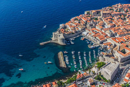 Aerial helicopter shoot of Dubrovnik old town harbor and st  John fortress  photo