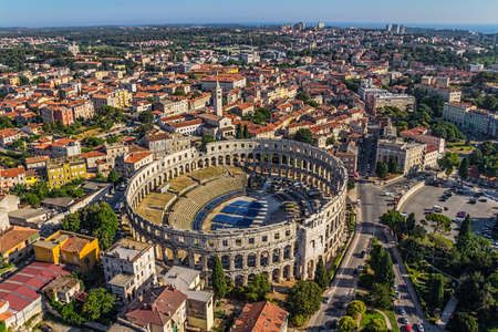 colonade: Roman time arena in Pula, with Monastery and Church of St. Anthony in the back, Croatia.