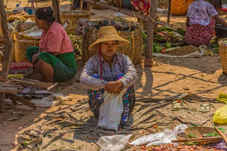 BAGAN, MYANMAR - FEBRUARY 24: Women are selling vegetables at the local market on February 24, 2013 in Bagan, Myanmar.