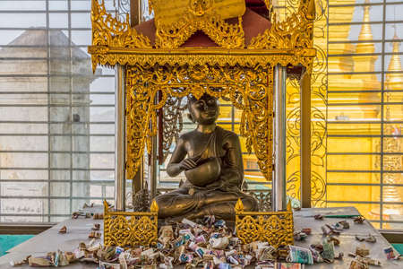 pious: MOUNT POPA, MYANMAR - FEBRUARY 24: Buddha statue with alms in Popa Taungkalat monastery atop an outcrop of volcano on February 24, 2012 in Mount Popa, Myanmar.