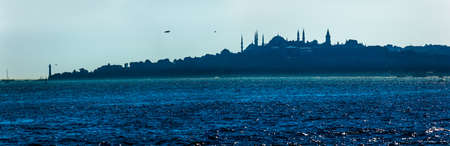 View of the beautiful blue Istanbul sailing Bosphorus. Topkapi, Hagia Sophia and Blue mosque on the horizon in the evening mist. photo