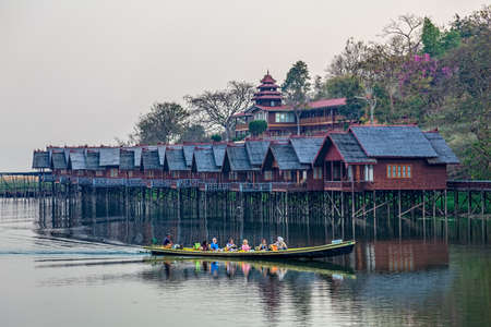 engineered: INLE LAKE, MYANMAR - FEBRUARY 28, 2013: Replica of the traditional floating village engineered as a hotel with bungalows with tourists returning from a lake trip.