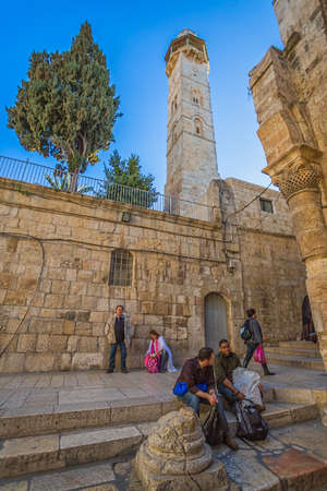 jaffa: JERUSALEM, ISRAEL - FEBRUARY 28, 2014: People resting in front of the Omer mosque minaret.