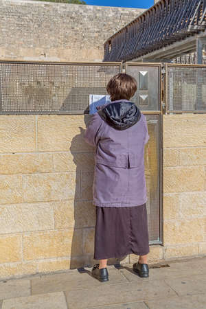 JERUSALEM, ISRAEL - FEBRUARY 28, 2014: Woman praying outside of the Wailing Wall, The Western Wall or Kotel which is located in the Old City at the foot of the western side of the Temple Mount.