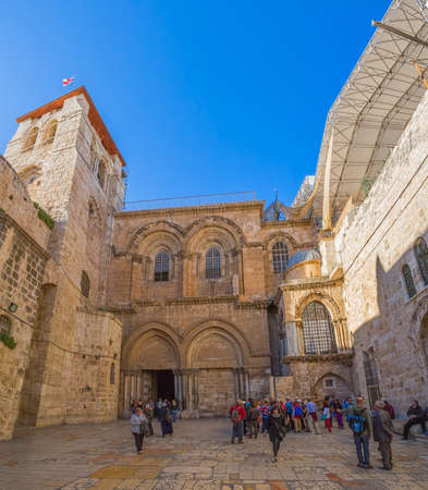 JERUSALEM, ISRAEL - FEBRUARY 28, 2014: Tourists and pilgrims sightseeing main entrance at the Church of the Holy Sepulchre in Old City.