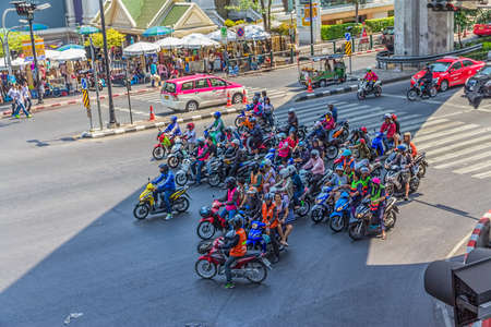 notorious: BANGKOK, THAILAND, MARCH 2, 2013: Motorcyclists wait at traffic lights in the shade under the bridge. Bangkoks traffic is notorious for traffic jams.