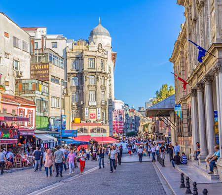 eminonu: ISTANBUL, TURKEY - SEPTEMBER 27, 2013: People walking in Old street Eminonu district with cafes and shops, afternoon city life.