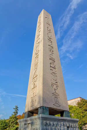 The Obelisk of Theodosius at Sultanahmet park and the moon in the blue sky. It is the Ancient Egyptian obelisk of Pharaoh Tutmoses III. photo