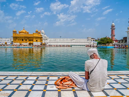 gurudwara: AMRITSAR, INDIA - MARCH 30, 2010: Sikh devotee sitting by the pool in front of the Golden Temple while Tourists and pilgrims entering  and walk towards The Harmandir Sahib Golden Temple, holiest shrine of the Sikh religion.