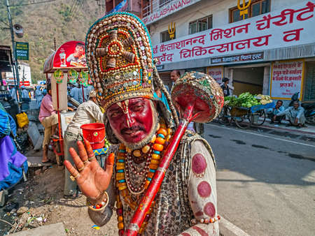 third eye: RISHIKESH, INDIA - APRIL 4, 2010: A man dressed as Hanuman offers blessings putting a sign on your forehead, third eye. Editorial