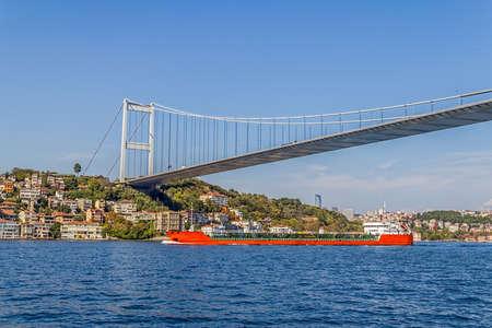 mehmet: Long red transport ship sailing under the Fatih Sultan Mehmet Bridge.