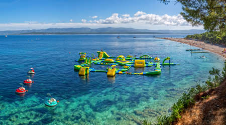 awarded: BOL, CROATIA - JULY 23, 2014: Zlatni Rat beach awarded with the Blue Flag and its water fun park that is amazing.