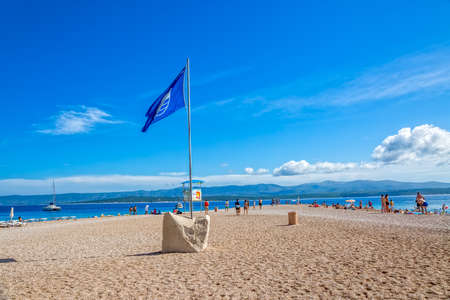 prestigious: BOL, CROATIA - JULY 23, 2014: Zlatni Rat beach awarded with the Blue Flag a prestigious international environmental awards that symbolize the purity of the sea, beach quality and safety of bathers Editorial