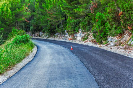 Traffic cone on a newly paved road through the forest photo