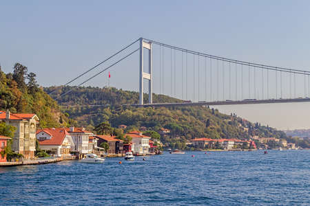 fatih: ISTANBUL, TURKEY - SEPTEMBER 29, 2013: View of the first raw of the waterfront houses in Kanlica and Fatih Sultan Mehmet Bridge sailing Bosphorus. Editorial
