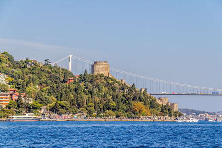 residental: ISTANBUL, TURKEY - SEPTEMBER 29, 2013: View of the Rumelihisari castle and Fatih Sultan Mehmet Bridge sailing Bosporus.
