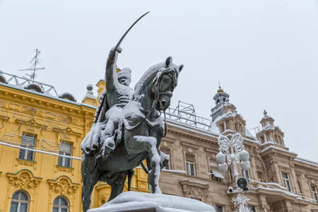 cavalryman: ZAGREB, CROATIA - December 28, 2014: Winter scene of the main square Ban Jelacic with sculpture covered with the snow.