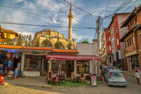 disorganized: Pristina, Kosovo - July 29, 2014 Two men resting with coffee under Fatih Mosque located in the center of the old town witch is disorganized and full of cables and wires.