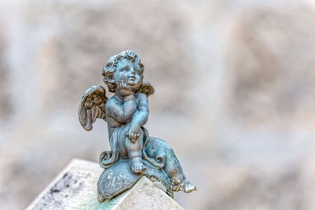 angel cemetery: Miniature angel statue sitting, decoration on the old catholic cemetery. Stock Photo