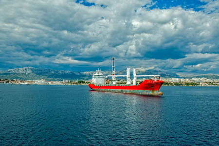 subsea: A large heavy lift ship anchored in front of the port. Stock Photo