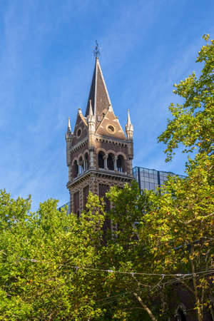 uniting: MELBOURNE, AUSTRALIA - MARCH 16, 2015: St Michaels Uniting Church tower with green tree top, famous landmark on the Collins and Russel Streets corner. Editorial