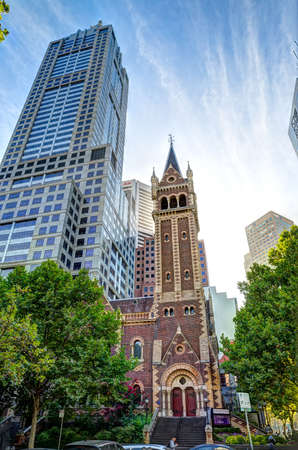 uniting: MELBOURNE, AUSTRALIA - MARCH 16, 2015: St Michaels Uniting Church tower with modern building, famous landmark on the Collins and Russel Streets corner. Editorial