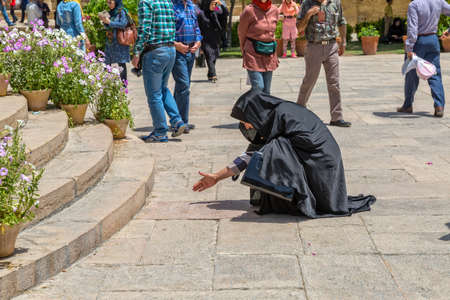 hafez: SHIRAZ, IRAN - MAY 2, 2015: A woman reads the verses carved in stone by the tomb of Hafez great poet. Editorial