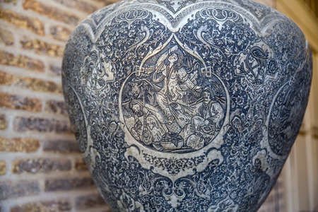 persia: SHIRAZ, IRAN - MAY 2, 2015: Engraved stories from hunting on a metal vase, traditional souvenir from Persia on Vakil Bazaar. Editorial