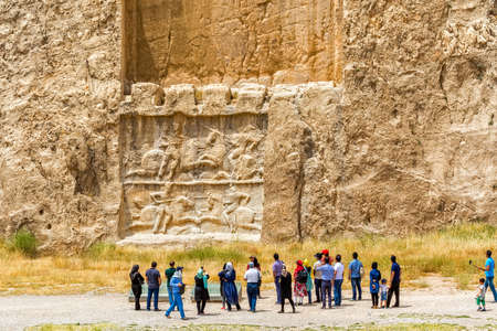 tour guide: NAQSH-E RUSTAM, IRAN - MAY 3, 2015: The group of tourists with the tour guide checking out the relief of the ancient necropolis near ruins of old city Persepolis. Editorial