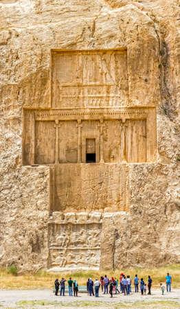 guia turistico: Naqsh-e Rostam, IR�N - 03 de mayo 2015: El grupo de turistas con el gu�a delante de los monumentos hist�ricos de la antigua necr�polis cerca de las ruinas de la antigua ciudad de Pers�polis.