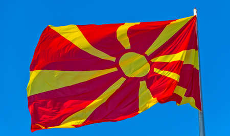 against the current: The current flag of Macedonia against blue sky