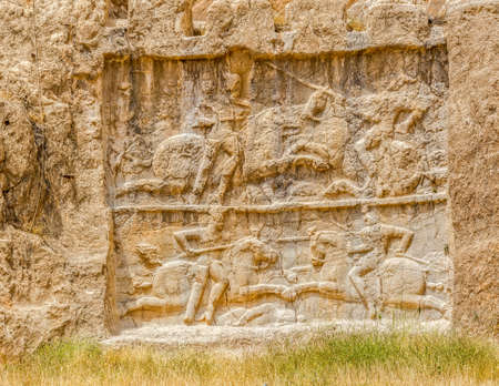 fars: Ancient relief of the necropolis Naqsh-e Rustam that shows the equestrian victory of Bahram II over enemy, near ruins of Persepolis.