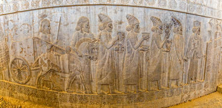 residents: Panorama of the stone bas-relief of residents of historical empire with animals carved on the stairway facade of the Apadana at the old city Persepolis. Stock Photo